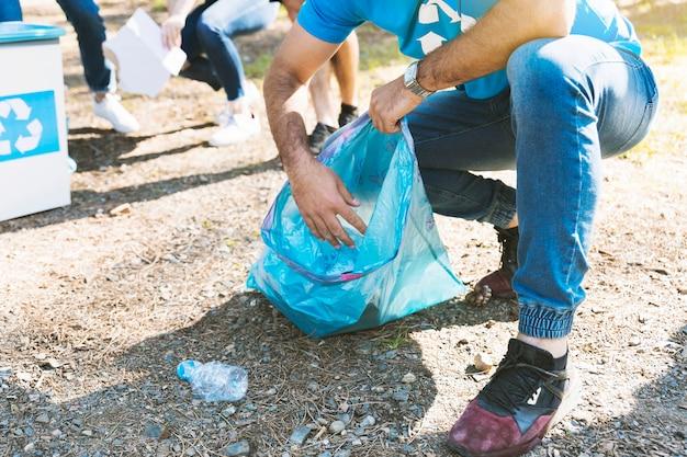 Mężczyzna zbiera śmieci w plastikowej torbie