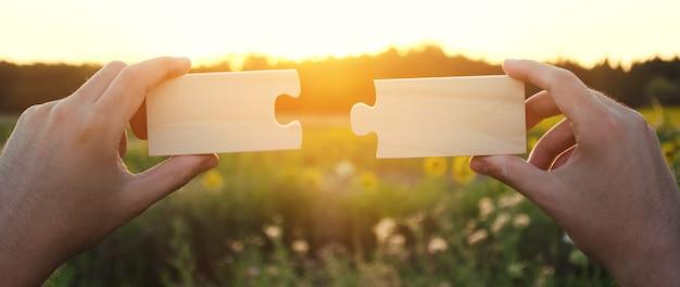 Mężczyzna zbiera, zbiera drewniane puzzle o zachodzie słońca.