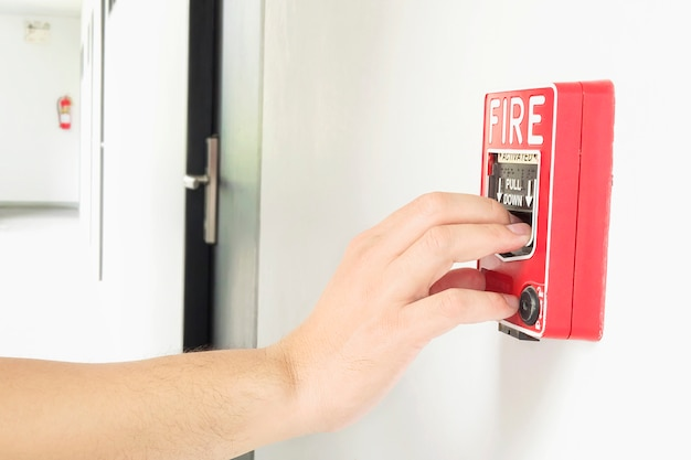 Mężczyzna zbliża się do dłoni, aby pchnąć stację alarmową przeciwpożarową