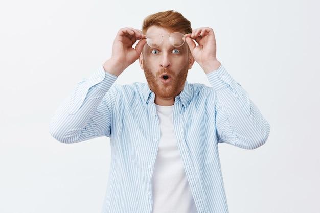 Mężczyzna zdejmujący okulary, widząc niesamowitą i zadziwiającą scenę, składający usta w wow, trzymający okulary na czole i patrząc pod wrażeniem i zaskoczeniem, jakby widział cud na szarej ścianie
