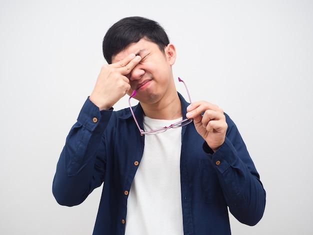 Mężczyzna zdejmuje okulary i czuje, że próbuje dotknąć jego oczu, azjata boli oczy od pracy