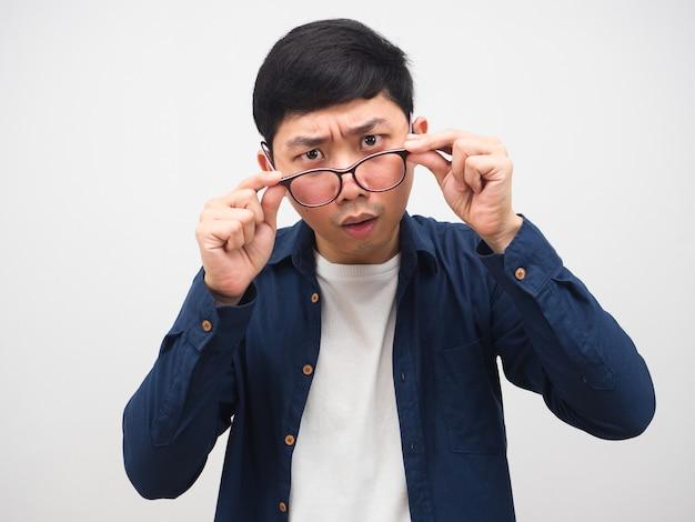Mężczyzna zdejmuje okulary i patrzy w kamerę, czując się zdezorientowany na swojej twarzy
