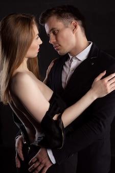 Mężczyzna zdejmuje sukienkę z seksownej kobiety, która delikatnie obejmuje go w momencie gry wstępnej.
