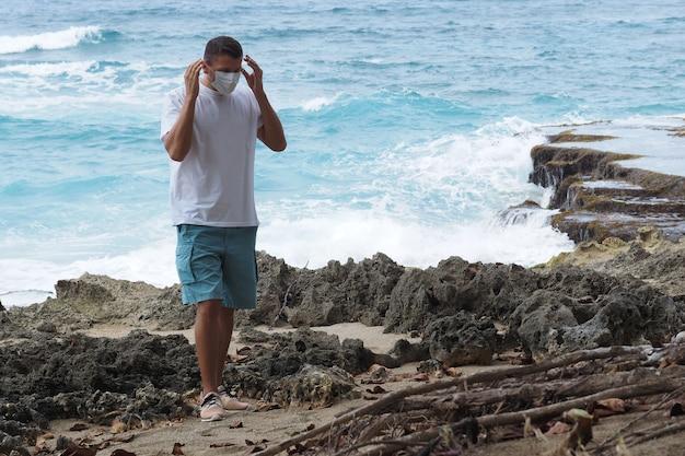 Mężczyzna zdejmuje / zakłada maskę medyczną stojącą na brzegu oceanu