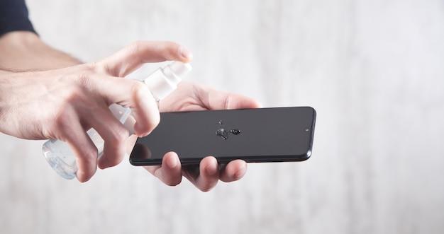 Mężczyzna zdezynfekuje smartfon żelem dezynfekującym.