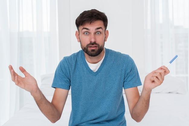 Mężczyzna zdumiony testem ciążowym
