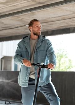 Mężczyzna ze skuterem na parkingu pod dachem