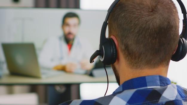 Mężczyzna ze słuchawkami podczas konsultacji online z lekarzem.