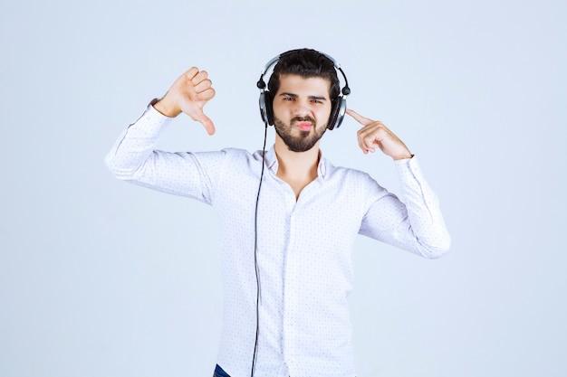 Mężczyzna ze słuchawkami pokazujący kciuk w dół