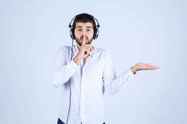 Mężczyzna ze słuchawkami pokazuje coś i prosi o ciszę