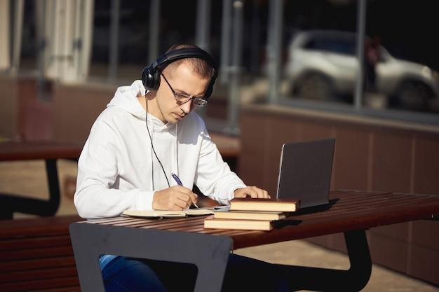 Mężczyzna ze słuchawkami pracuje na laptopie i pisze w zeszycie siedząc na ulicy przy stole