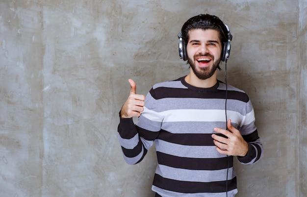Mężczyzna ze słuchawkami słucha muzyki i pokazuje znak satysfakcji