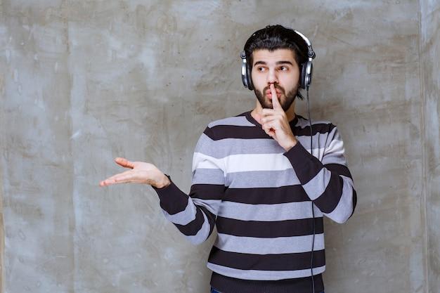 Mężczyzna ze słuchawkami słucha muzyki i prosi o ciszę