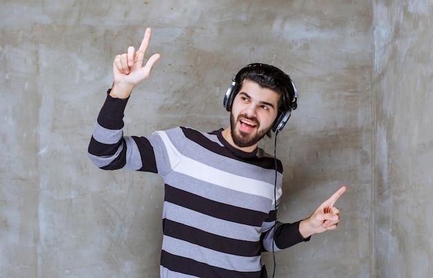 Mężczyzna ze słuchawkami słucha muzyki i tańczy