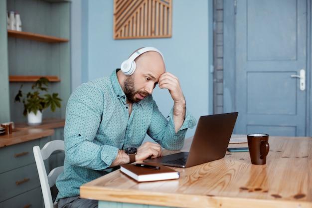 Mężczyzna ze słuchawkami sprawdza wyniki pracy z poprzedniego dnia