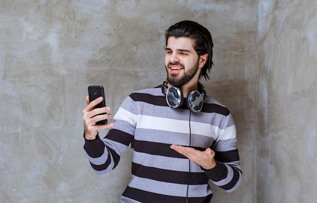 Mężczyzna ze słuchawkami sprawdzający swoje wiadomości lub playlistę z pozytywną energią