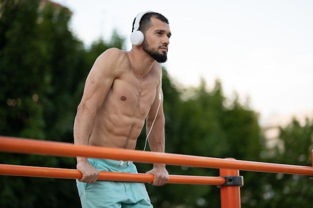 Mężczyzna ze słuchawkami w ciągu dnia pchający ups na barach na ulicy