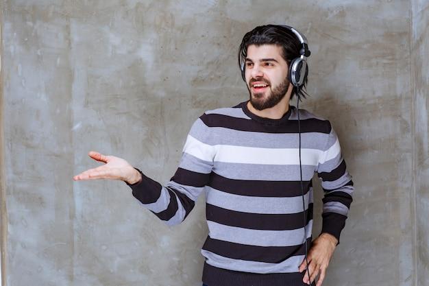 Mężczyzna ze słuchawkami wchodzący w interakcję z kimś na bok