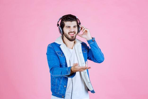 Mężczyzna ze słuchawkami wskazującymi na osobę po prawej