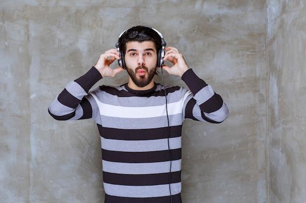 Mężczyzna ze słuchawkami wygląda na zaskoczonego i przerażonego