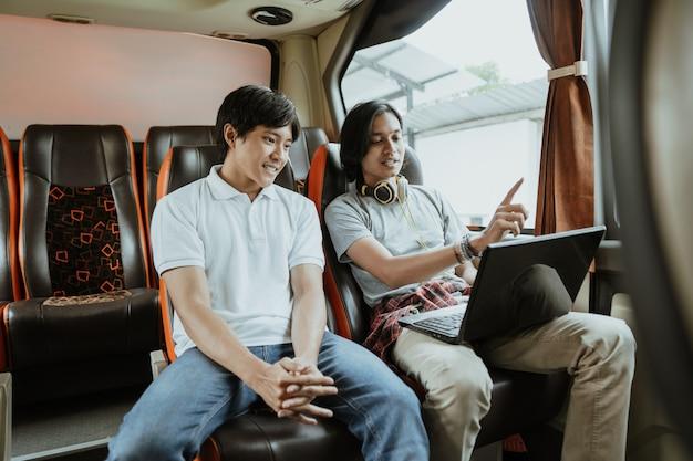 Mężczyzna ze słuchawkami wyjaśnia, jak korzystać z laptopa, rozmawiając z kolegą o pracy, siedząc przy oknie w autobusie