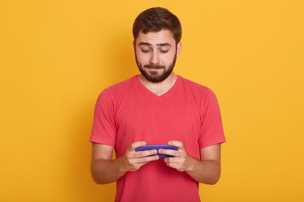 Mężczyzna ze spokojnym wyrazem twarzy, marzy o czerwonej koszulce na co dzień, grając w gry online na smartfonie lub sprawdzając swoją sieć społecznościową, pozowanie na żółtym tle. koncepcja technologii
