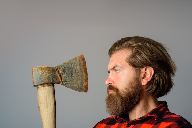 Mężczyzna ze starą siekierą brodaty drwal brodaty mężczyzna z siekierą obok twarzy z bliska portret mężczyzny z siekierą