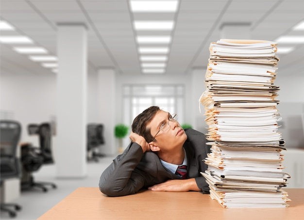 Mężczyzna ze stosem folderów z dokumentami w tle