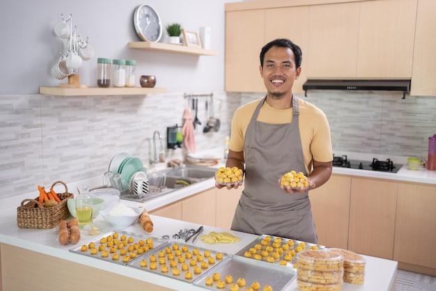 Mężczyzna ze swoim gotowaniem uśmiecha się do kamery robi ciasto nastar na eid mubarak w domu