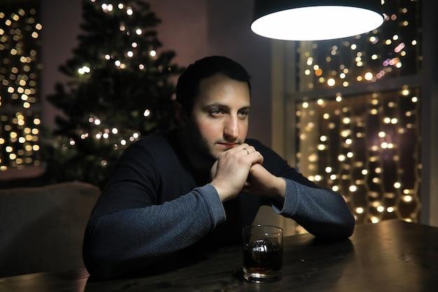Mężczyzna ze szklanką whisky w pubie w nocy