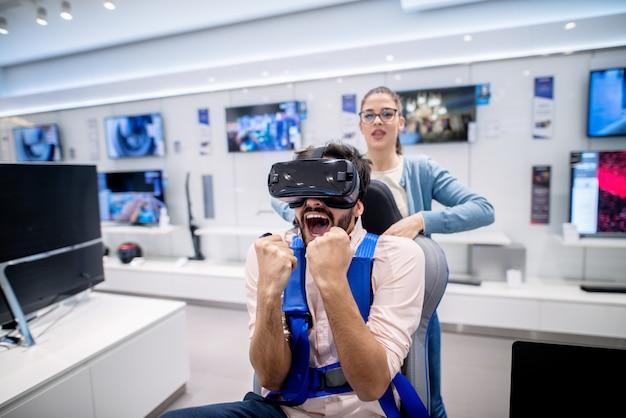 Mężczyzna ze zdumionym wyrazem twarzy wypróbowuje technologię vr. kobieta stojąca za jego plecami. wnętrze sklepu technicznego.