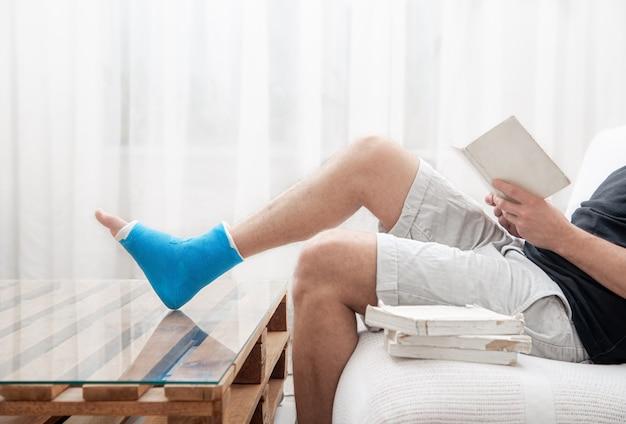 Mężczyzna ze złamaną nogą w gipsie czyta książki na jasnym tle wnętrza pokoju.