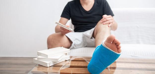 Mężczyzna ze złamaną nogą w niebieskiej szynie do leczenia urazów po zwichnięciu stawu skokowego, czytanie książek na rehabilitacji domowej.