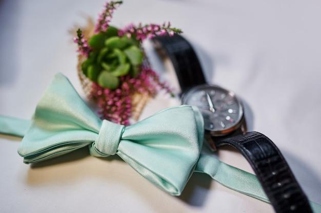 Mężczyzna zegarki i turkusowy motyl na stole.