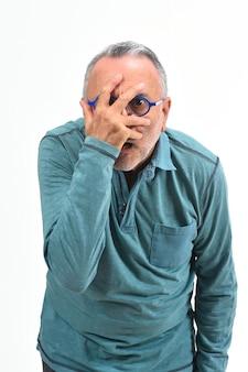 Mężczyzna zerkanie z ręką na twarzy na bielu