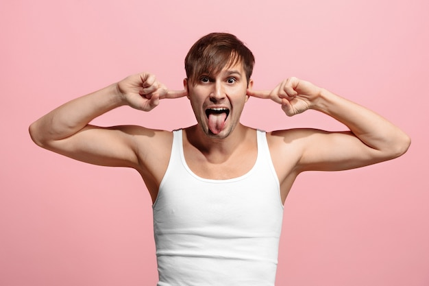Mężczyzna zezujący ze dziwnym wyrazem twarzy na różowej ścianie