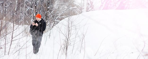 Mężczyzna zimą w lesie. turysta z plecakiem przemierza zimą lasy. podejście zimowe.