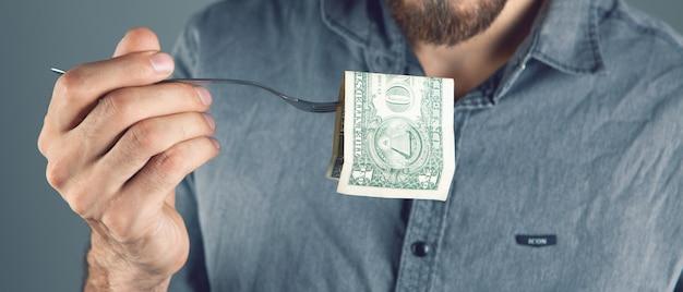 Mężczyzna zjada pieniądze widelcem