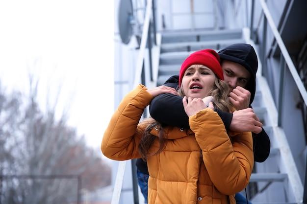 Mężczyzna złodziej atakuje młodą kobietę na zewnątrz