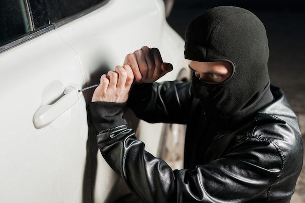 Mężczyzna złodziej otwiera drzwi samochodu za pomocą śrubokręta