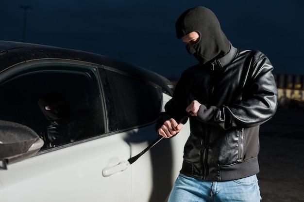 Mężczyzna złodziej samochodów otwiera drzwi z jemmy