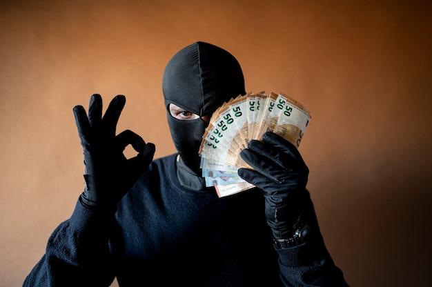 Mężczyzna złodziej z kominiarką na głowie trzymający przed oczami garść rachunków w euro, robiąc ok gest
