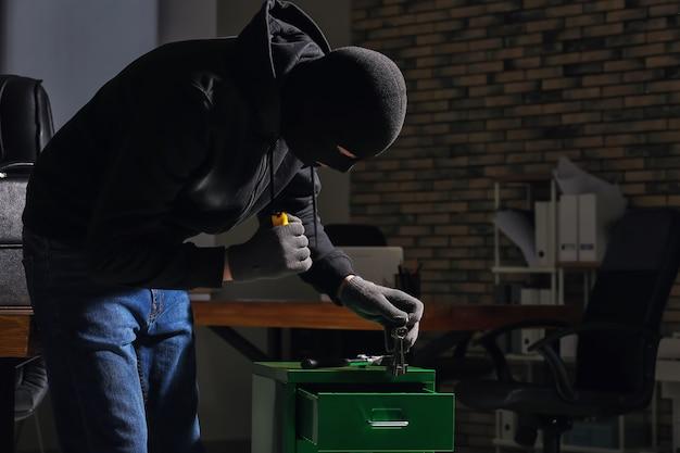 Mężczyzna złodziej z latarką w biurze