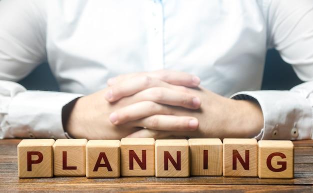 Mężczyzna złożył ręce na tle bloków z napisem planning leadership quality