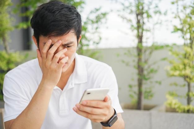 Mężczyzna zmarszczył brwi z poważnym uczuciem podczas surfowania po internecie, szukając komentarza w mediach społecznościowych