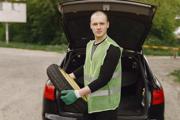 Mężczyzna zmienia łamanego koło na samochodzie