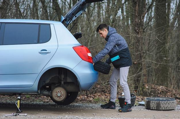 Mężczyzna zmienia oponę z kołem w samochodzie
