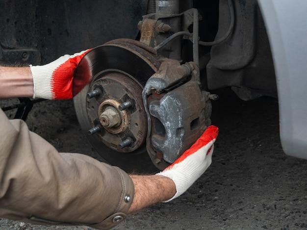 Mężczyzna zmienia opony letnie samochodu na zimę