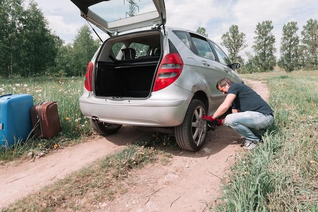 Mężczyzna zmienia przebitą oponę w swoim samochodzie. kłopoty na drodze