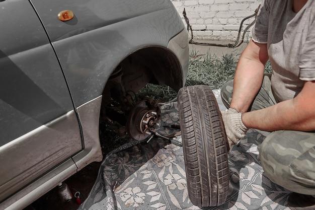 Mężczyzna zmienia uszkodzone koło swojego samochodu.